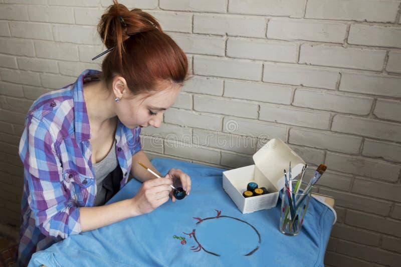 Foto van meisje dat tekenings acrylverven op blauwe kleren royalty-vrije stock afbeeldingen