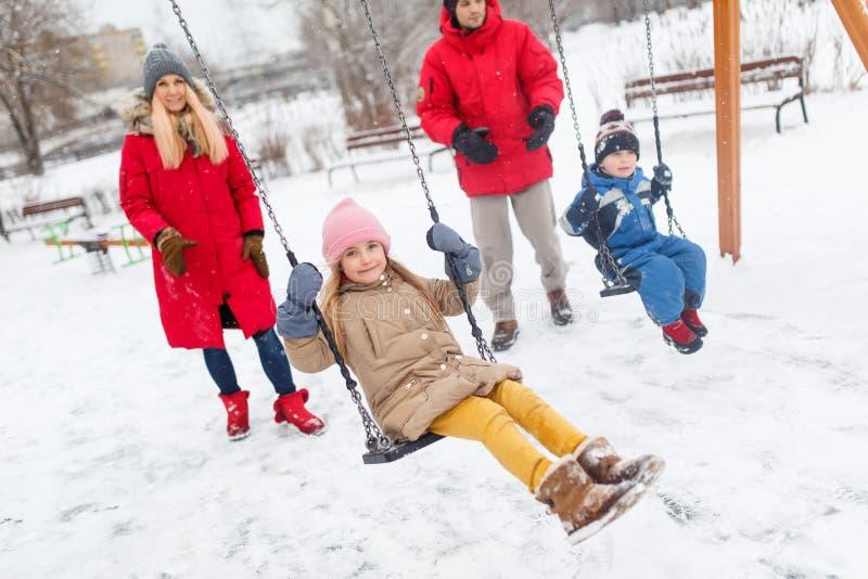 Foto van meisje en jongen die in de winter in park met ouders slingeren royalty-vrije stock foto's