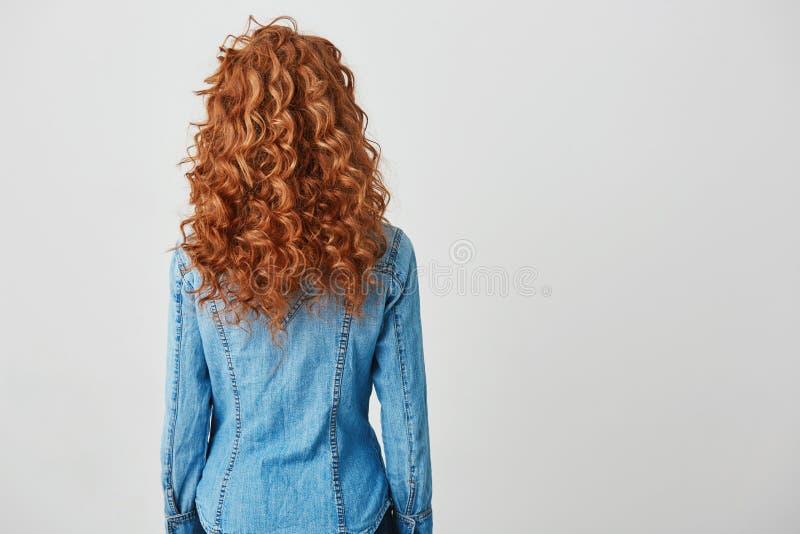 Foto van meisje met rood krullend haar die zich terug naar camera over witte achtergrond bevinden De ruimte van het exemplaar royalty-vrije stock afbeelding