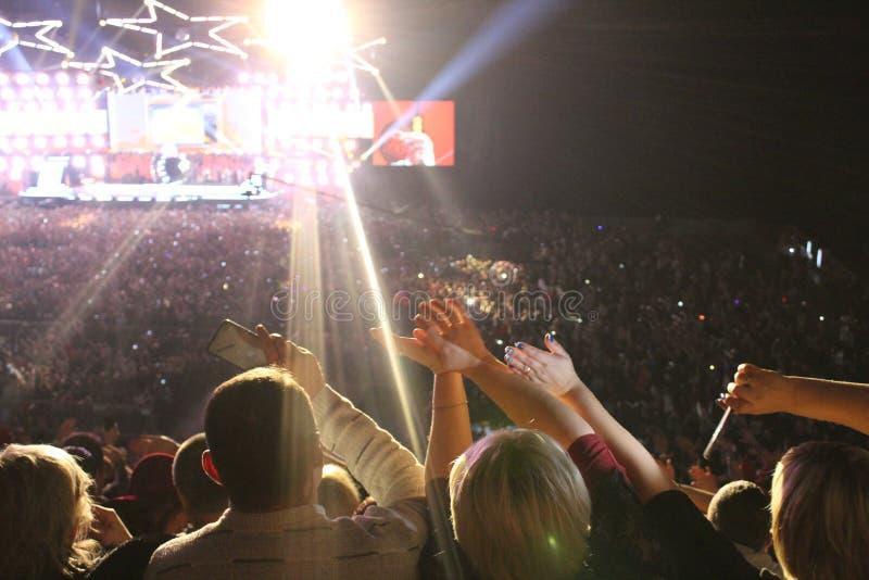 Foto van mensen bij het overleg in de grote zaal met hun omhoog handen stock afbeelding