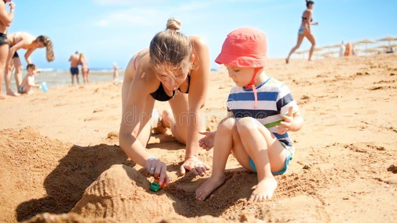 Foto van moeder met weinig zoon de bouwzandkasteel op het overzeese strand Mensen die bij oceaan ontspannen Familie die rusten en royalty-vrije stock foto's