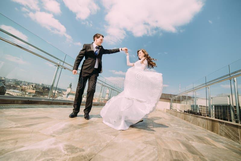 Foto van mooie bruid en bruidegom die op dakbovenkant bij zonnige dag dansen stock afbeeldingen