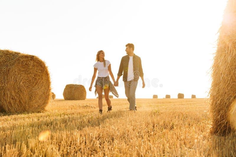 Foto van mooie van de paarman en vrouw het lopen hand met de hand thr stock fotografie