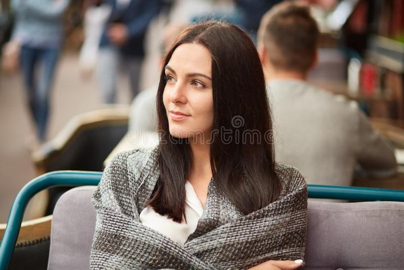 Foto van mooie donkerbruine opzij geconcentreerde die vrouw, in sprei wordt de verpakt, denkt over iets met nadenkende uitdrukkin stock afbeelding