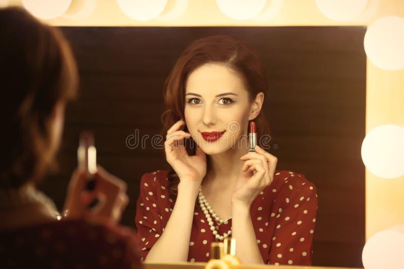 Foto van mooie jonge vrouw die haar lippenstift houden dichtbij de winst royalty-vrije stock afbeelding