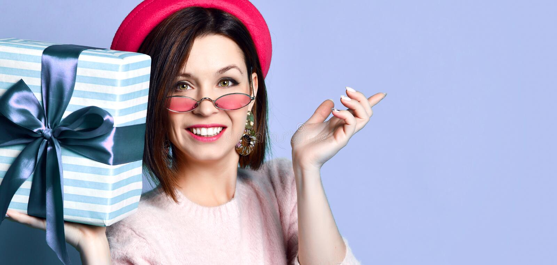 Foto van mooie vrouw in vilten hoed die huidige giftdoos houden stock afbeelding