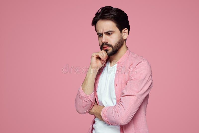Foto van nadenkend die mannetje over roze muur wordt geïsoleerd als achtergrond royalty-vrije stock foto's