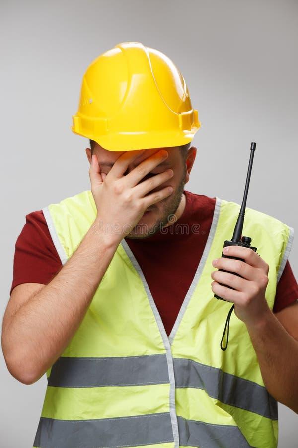 Foto van ongelukkige bouwer in gele helm met walkie-talkie op lege grijze achtergrond stock foto's