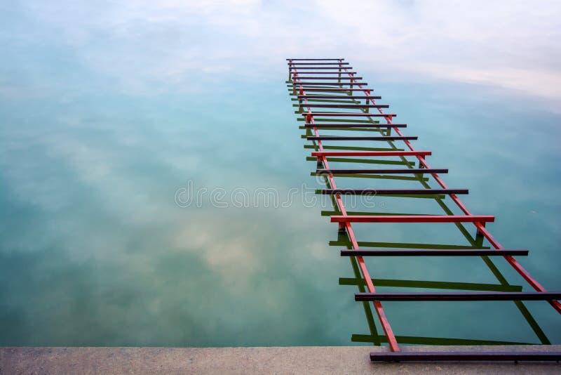 Foto van onvolledig weinig brug op het meer, abstracte brug aan hemel stock afbeelding