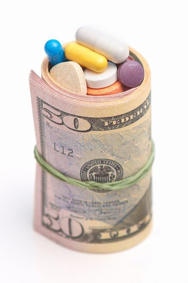Foto van opgerolde dollars en vele pillen binnen Geld en drugs Geneeskundeprijs Geneeskundehulp Corruptie en de slechte dienst zo stock afbeelding