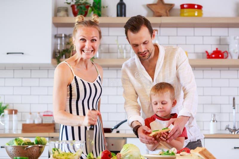 Foto van ouders en jonge zoon die voedsel in keuken voorbereiden royalty-vrije stock afbeeldingen