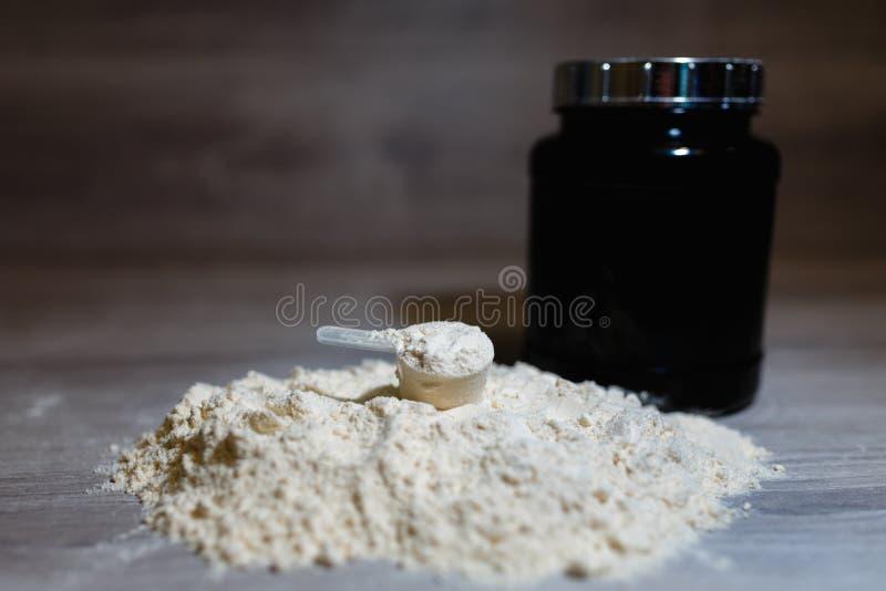 Foto van product lepel of het meten van lepel van weiproteïne op zwarte plastic kruikachtergrond met deksel op grijze houten acht royalty-vrije stock foto's