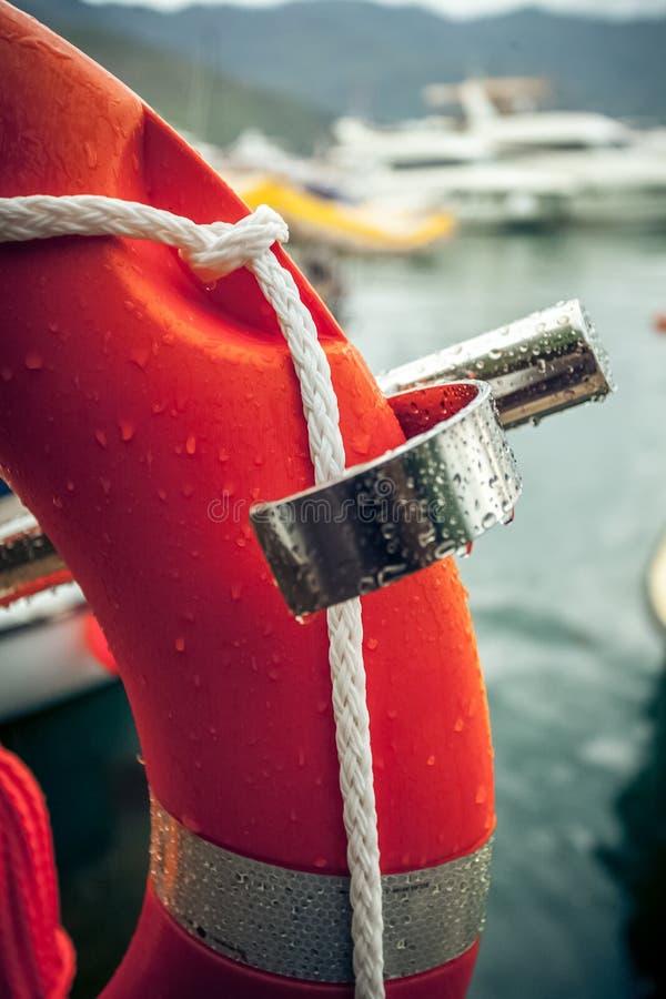 Foto van rode reddingsboei met kabel tegen zeehaven royalty-vrije stock afbeeldingen