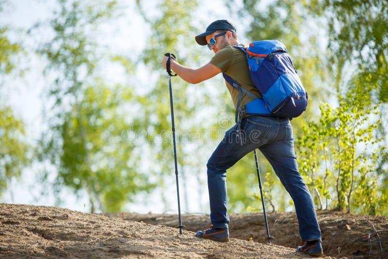 Foto van rug van de mens met rugzak en wandelstokken op heuvel stock foto's