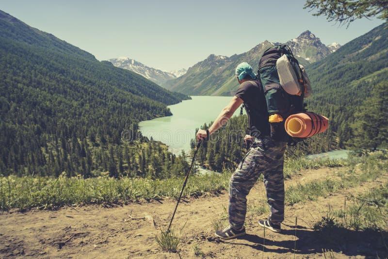 Foto van rug van de toeristenmens met wandelstokken met zijn handen omhoog op bergheuvel dichtbij meer de stokken van de toeriste stock fotografie