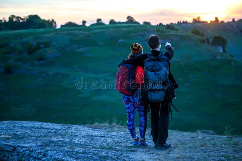 Foto van rug van het koesteren van de mens en toeristenvrouw met rugzakken op berg royalty-vrije stock foto