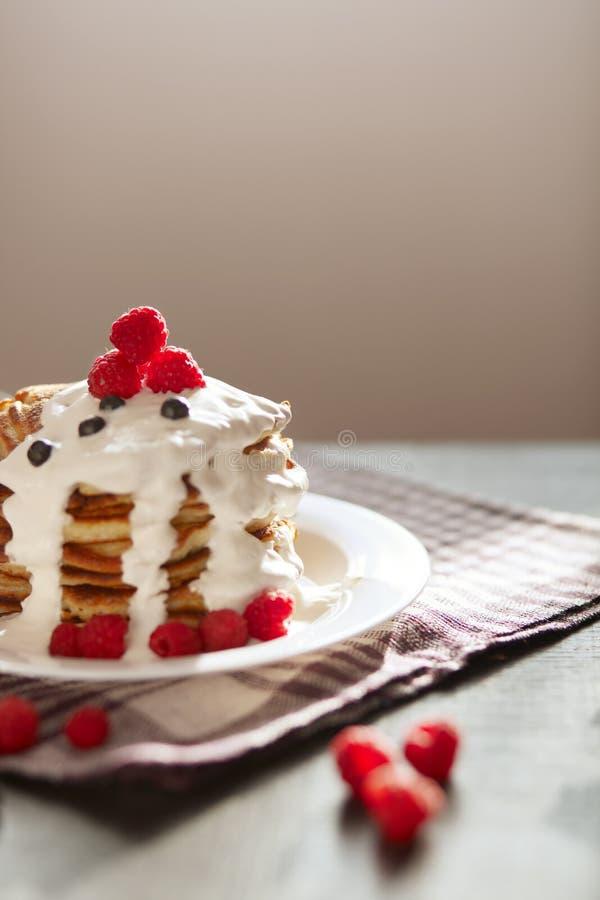 Foto van smakelijke die pannekoeken met bosbessen en frambozen, witte plaat met muffins op lijst, heerlijke swwetschotel worden v royalty-vrije stock afbeelding