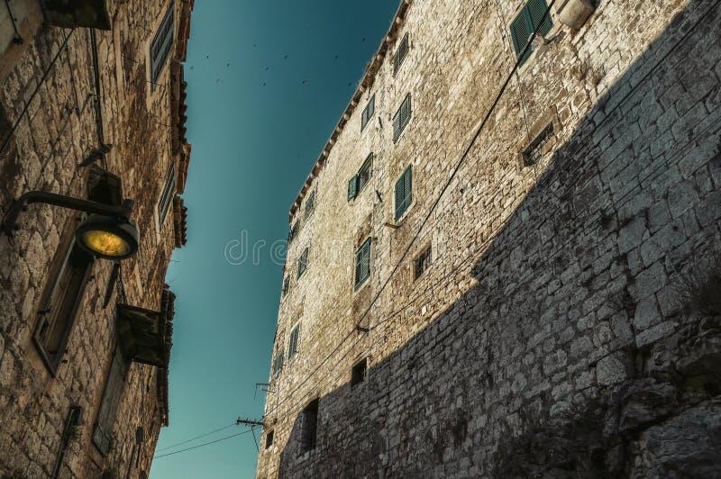Foto van smalle straat van neer in Sibenik Kroatië met troep van vogels boven de muren Historische huizen op straat met lamp stock fotografie