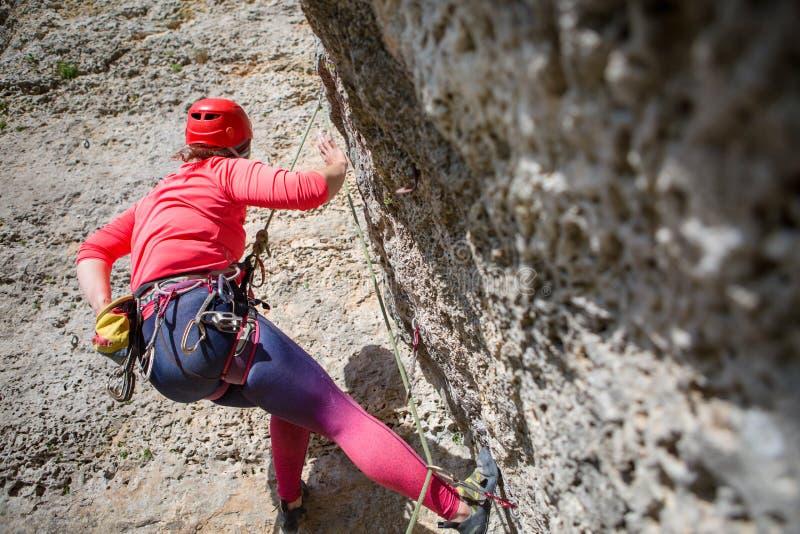Foto van sportenvrouw in rode bouwvakker die omhoog beklimmend op berg kijken royalty-vrije stock fotografie