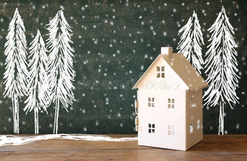 Foto van stuk speelgoed huis voor bord met de tekeningen van het de winterconcept stock fotografie