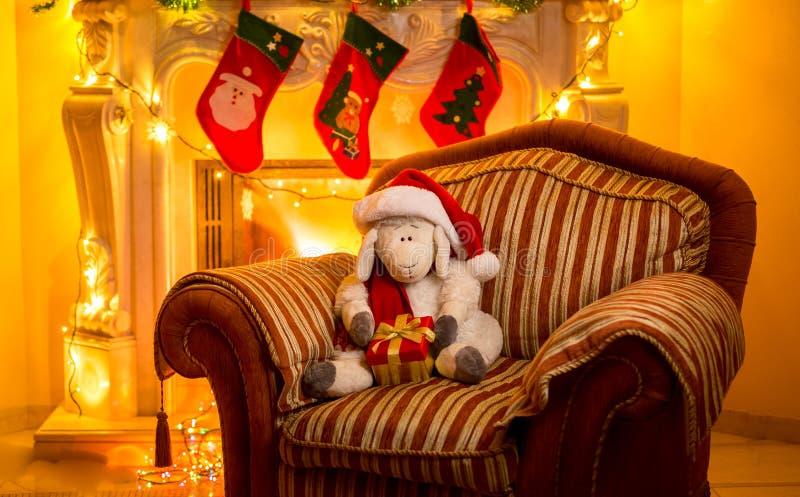 Foto van stuk speelgoed lamszitting op stoel bij open haard in Christma royalty-vrije stock afbeeldingen