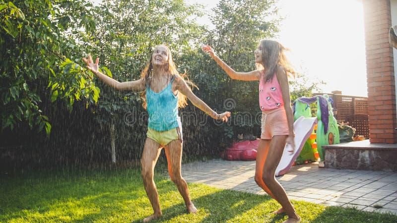 Foto van twee gelukkige lachende zusters in natte kleren die onder waterdruppeltjes van tuinslang bij tuin dansen Familie stock afbeeldingen