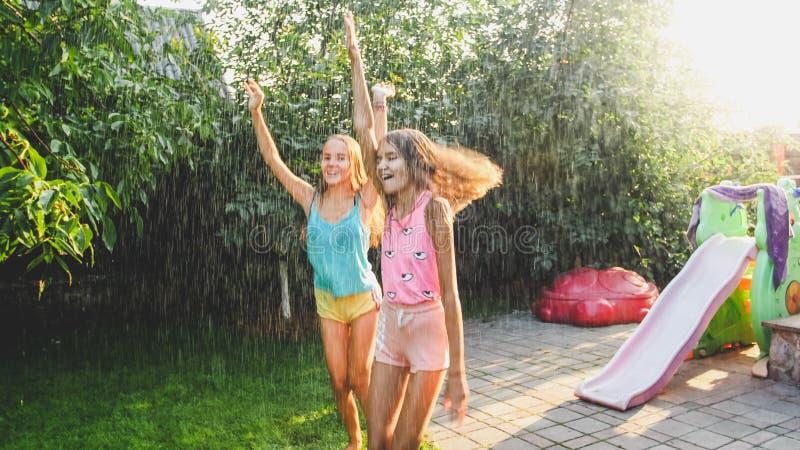 Foto van twee gelukkige lachende zusters in natte kleren die onder waterdruppeltjes van tuinslang bij tuin dansen Familie royalty-vrije stock afbeeldingen