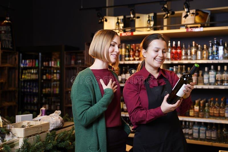 Foto van twee gelukkige vrouwen met fles wijn stock afbeelding