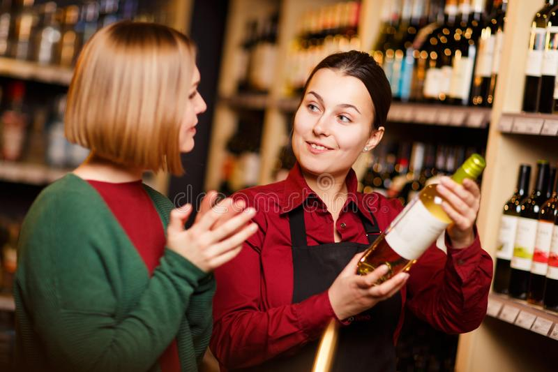 Foto van twee jonge vrouwen met fles in handen bij slijterij stock foto