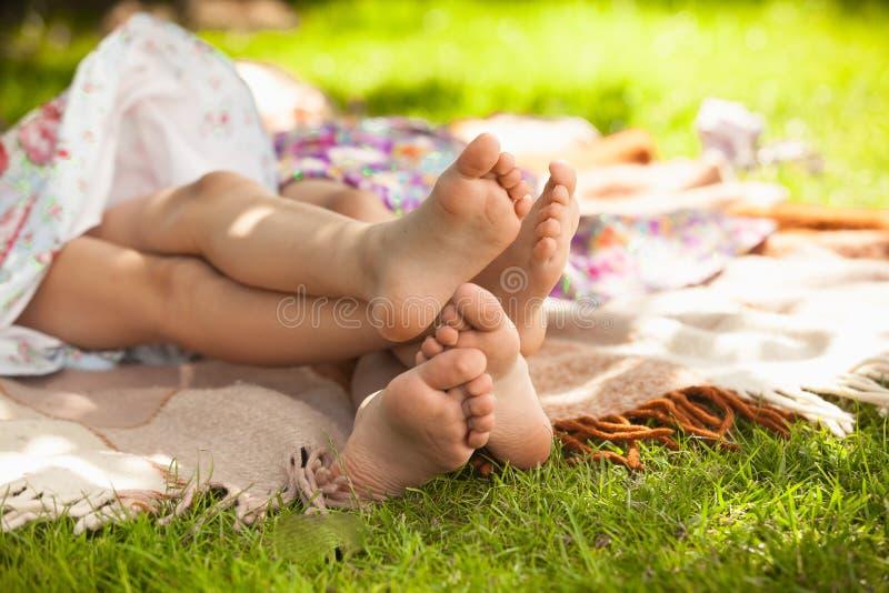 Foto van twee meisjesvoet die op gras liggen en pret hebben royalty-vrije stock foto