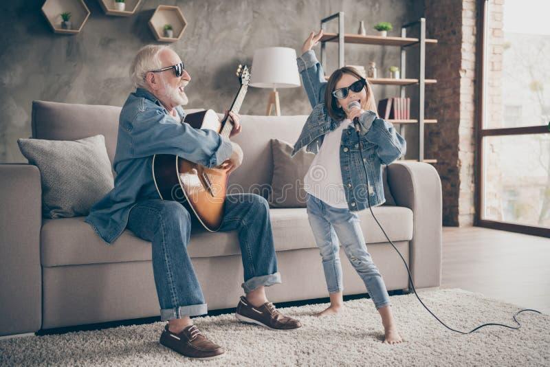 Foto van twee mensen die opa guitar kleindochter mic speelt en die vrolijke, coole stijl trendy sun specs zingt denim royalty-vrije stock afbeeldingen