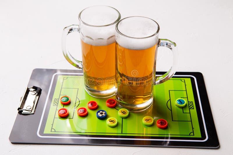Foto van twee mokken schuimend bier, lijstvoetbal stock foto