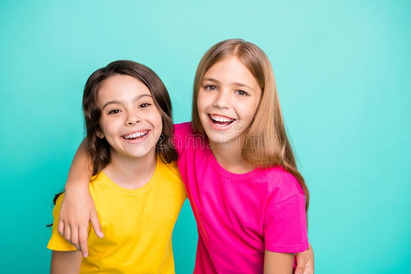 Foto van twee vriendelijke, prachtige, mooie meisjes die blij zijn om gefotografeerd te worden terwijl ze geïsoleerd zijn met de  stock afbeelding