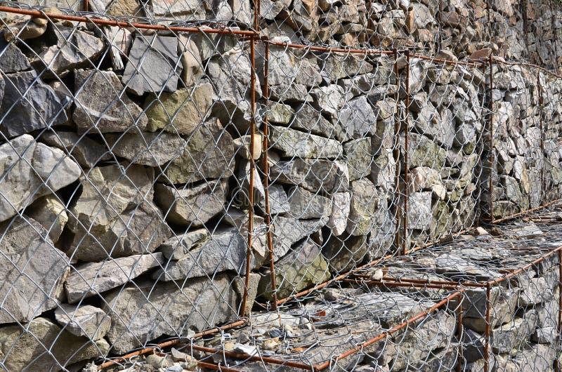 Foto van verscheidene gabions De netwerkcellen van de kubieke vorm worden gevuld met bergstenen van diverse vormen die waterthrou royalty-vrije stock foto