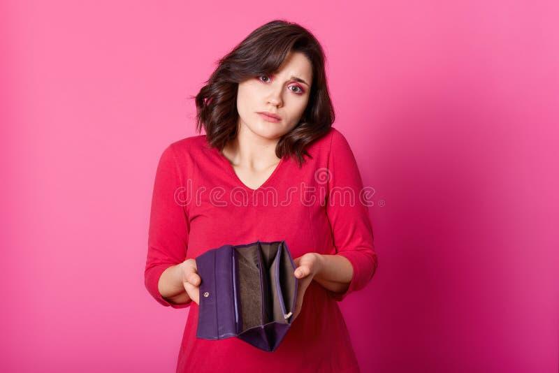 Foto van verstoord brunette met geopende portefeuille in handen De mooie droevige vrouw drukt schouders en khow hoe te betaalt ni royalty-vrije stock foto