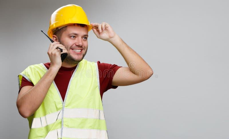 Foto van vrolijke bouwer in gele helm die op radio in studio spreken stock afbeeldingen