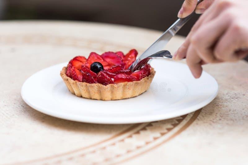 Foto van vrouwelijke handen die een fruitcake met aardbeien snijden stock foto's