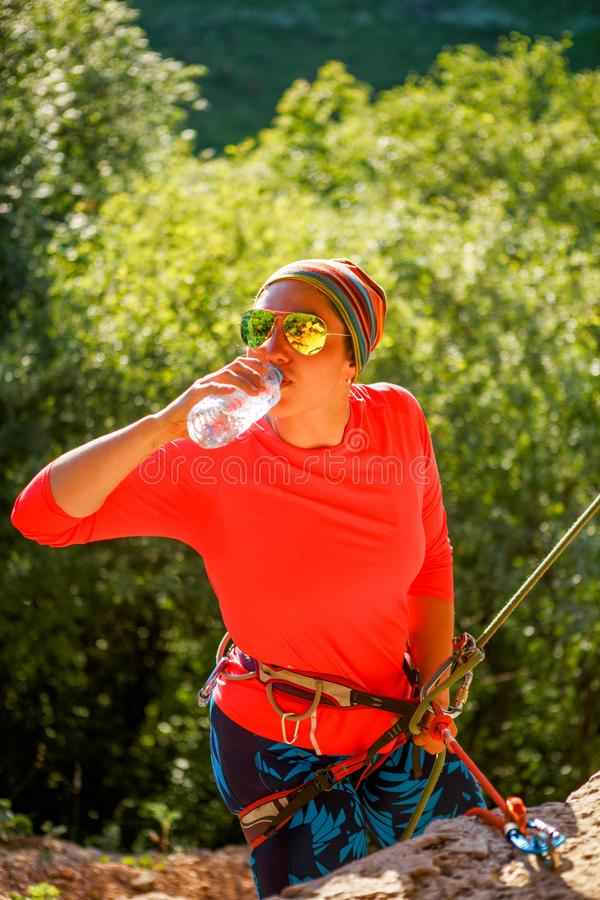 Foto van vrouwenklimmer in de zitting van het zonnebril drinkwater naast berg stock afbeelding