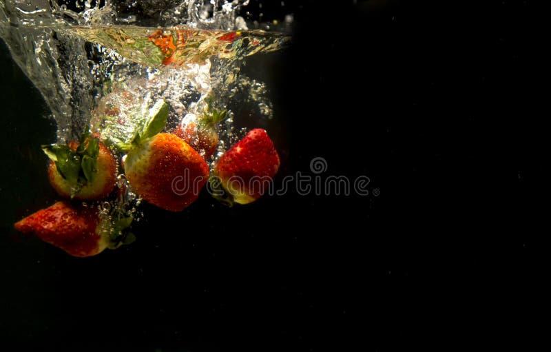 Foto van vruchten onder water worden gelaten vallen dat stock afbeelding