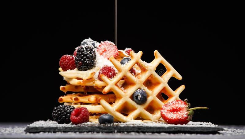 Foto van Weense die wafeltjes met frambozen, aardbeien met gepoederde suiker, met honing op zwarte leeg worden bestrooid stock foto