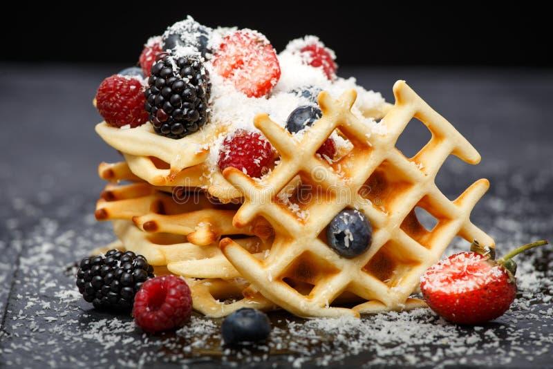 Foto van Weense wafeltjes met verse die frambozen, aardbeien met gepoederde suiker op bord tegen spatie worden bestrooid royalty-vrije stock foto