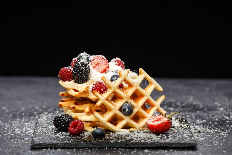 Foto van Weense wafeltjes met verse die frambozen, aardbeien met gepoederde suiker op bord tegen spatie worden bestrooid stock foto's