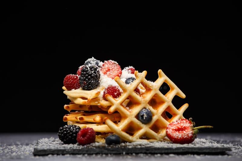 Foto van Weense wafeltjes met verse die frambozen, aardbeien met gepoederde suiker op bord tegen spatie worden bestrooid royalty-vrije stock fotografie
