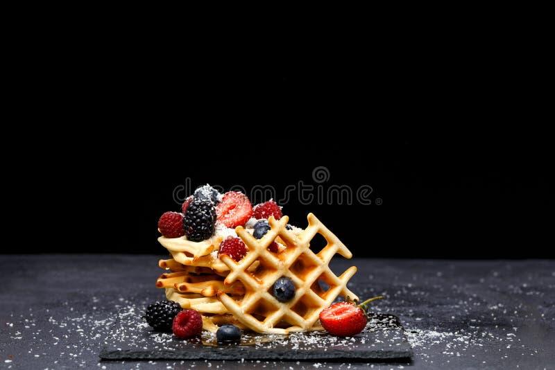 Foto van Weense wafeltjes met verse die frambozen, aardbeien met gepoederde suiker op bord tegen spatie worden bestrooid stock afbeelding