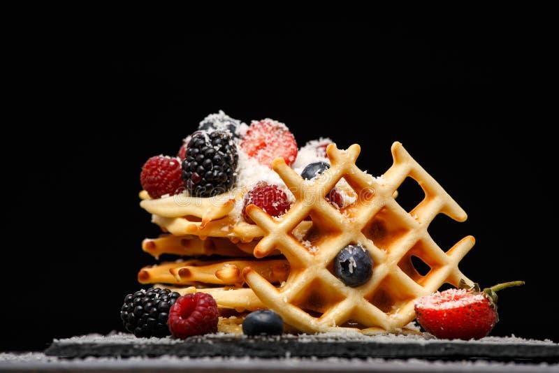 Foto van Weense wafeltjes met verse die frambozen, aardbeien met gepoederde suiker op bord tegen spatie worden bestrooid royalty-vrije stock afbeeldingen