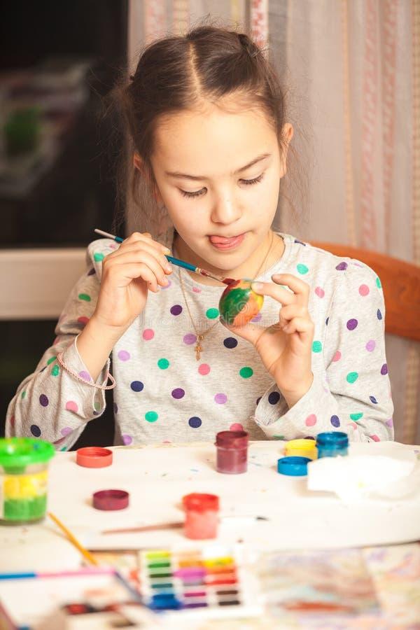 Foto van weinig ijverig meisje die paasei schilderen royalty-vrije stock afbeeldingen