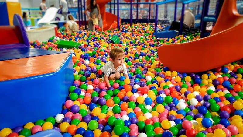 Foto van weinig jongen die in het poolhoogtepunt spelen van colroful plastic ballen Peuter die pret op speelplaats in het winkele royalty-vrije stock afbeeldingen
