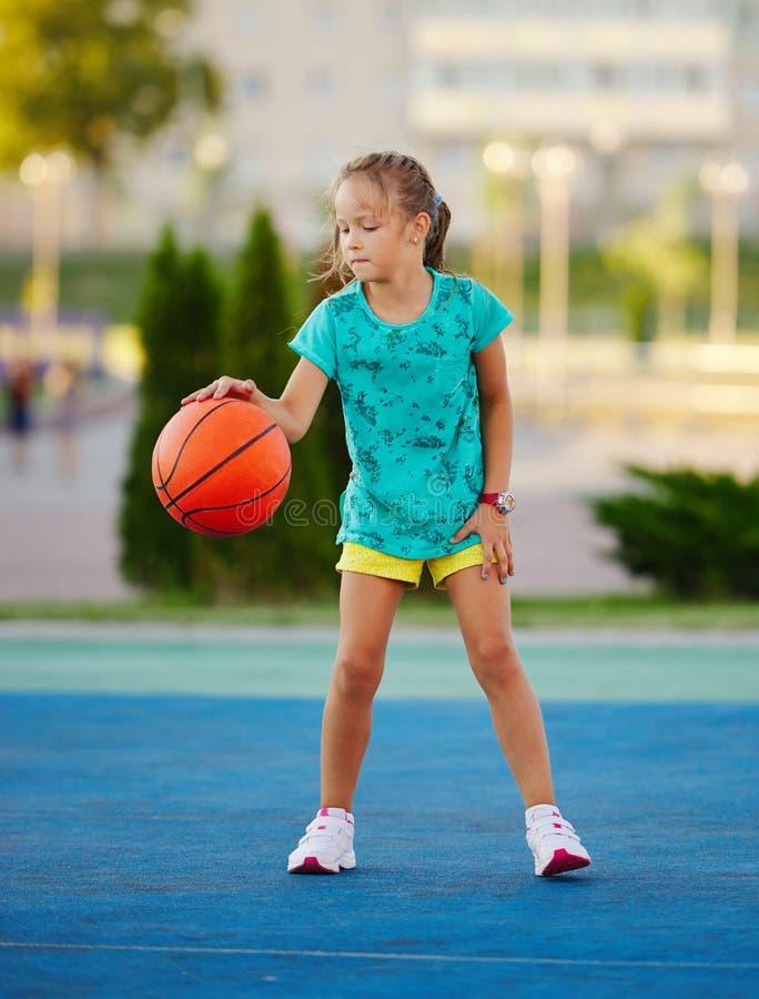 Foto van weinig leuk meisjes speelbasketbal in openlucht royalty-vrije stock afbeelding