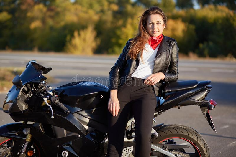 Foto van zelf verzekerde vrouw de gekleed in leerjasje, zwarte broeken, leunt op motor, heeft nadenkende uitdrukking, daarna rust stock afbeelding