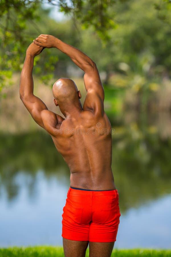 Foto van zich het jonge Afrikaanse Amerikaanse geschiktheid model uitrekken in het park Mens die shirtless tonende spieren stelle stock foto